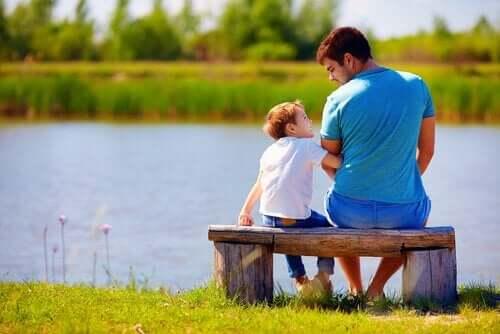 zu entschuldigen - Vater sitzt mit Sohn auf Bank am Fluss