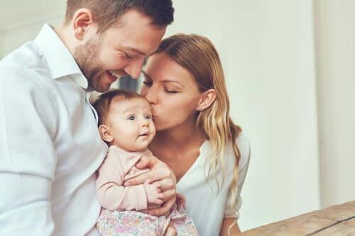 Eltern, die ihr Baby küssen.