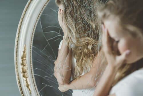 Glück und Angst - Frau vor einem zerbrochenen Spiegel