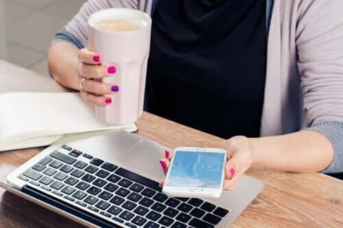 Smartphone - Frau mit Handy und Laptop