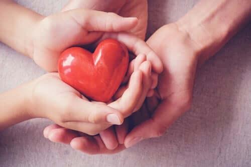 Entwicklung von Empathie - vier Hände halten ein Herz