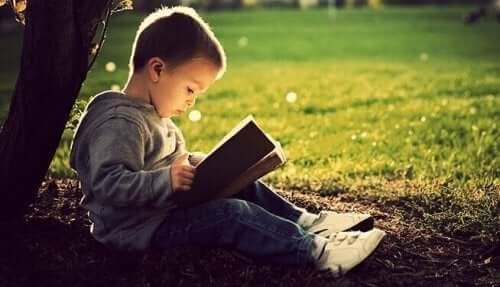 Ein kleiner Junge sitzt unter einem Baum und liest