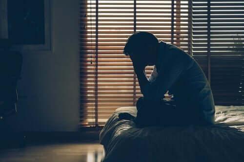 Psychosomatische Störungen und Stress - erschöpfter Mann sitzt auf einem Bett