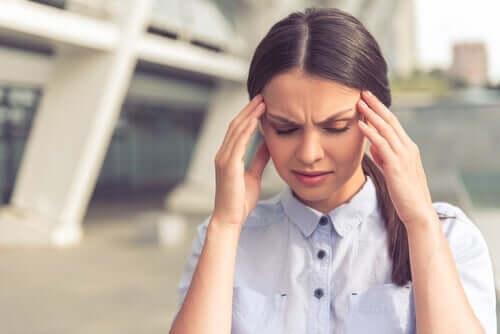 Psychosomatische Störungen und Stress - Frau mit Kopfschmerzen