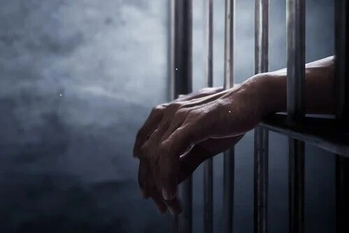 Hände einer Person hinter Gittern. Keine Kaution