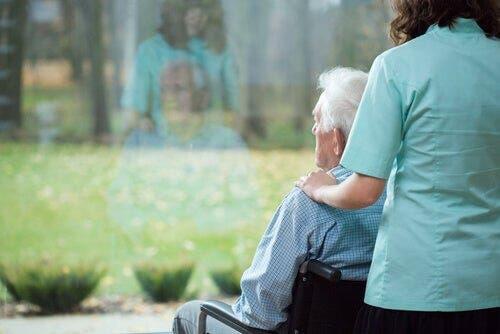 Huntington-Krankheit - Mensch im Rollstuhl blickt aus dem Fenster