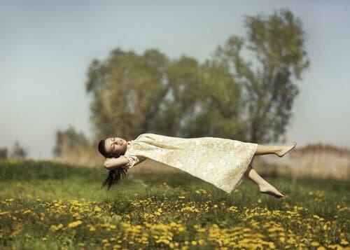 Halluzinationen - Frau schwebt über einer Wiese
