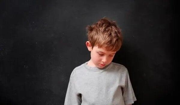 En trauriger Junge senkt den Kopf. SDQ-Fragebogen