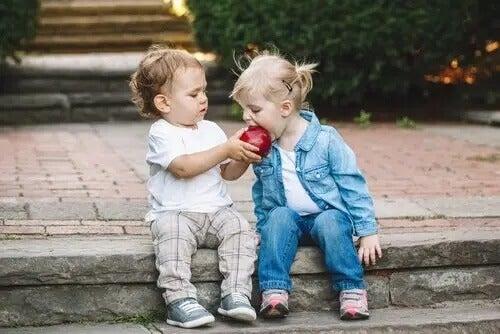 Zwei KInder teilen sich einen Apfel. SDQ-Fragebogen