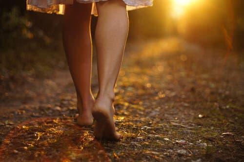 Lebensziel - Frau läuft barfuß im Wald