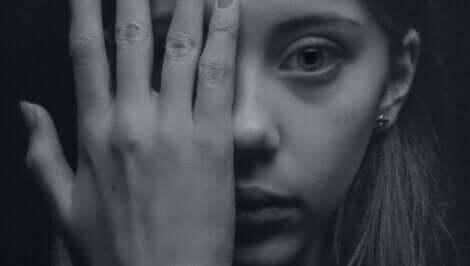 Schwächen akzeptieren - Frau bedeckt ein Auge mit ihrer Hand