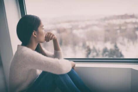 bewölkte Tage - traurige Frau am Fenster