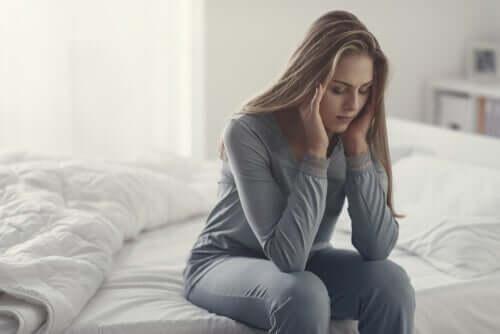 Angst als Verbündeten sehen - Frau sitzt auf dem Bett