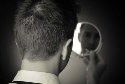 Body Dysmorphic Disorder - Mann betrachtet sich im Spiegel