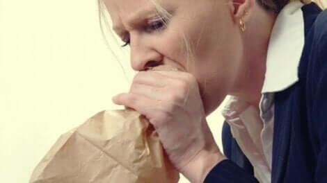 Hyperventilation - Frau atmet in Papiertüte