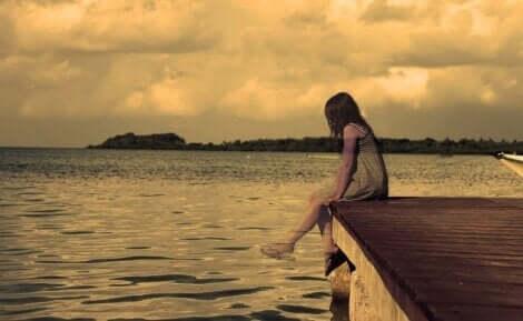 Warum Eltern ihre Kinder verlassen - Mädchen sitzt alleine an einem Steg