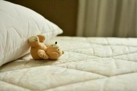 Ein Teddybärchen kippt von einem Kopfkissen.