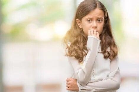 Ein Mädchen knabbert an ihren Fingernägeln.