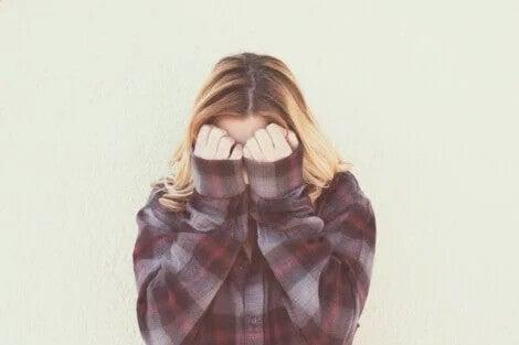 Ein junges Mädchen hält sich die Hände vor das Gesicht.