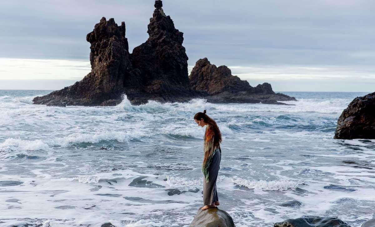 Alles schief - Frau auf einem Felsen im Meer