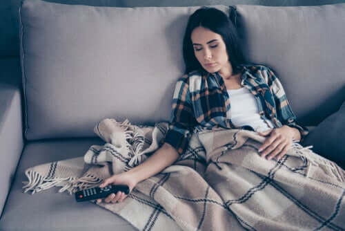 Ein sitzender Lebensstil - Frau schläft auf dem Sofa