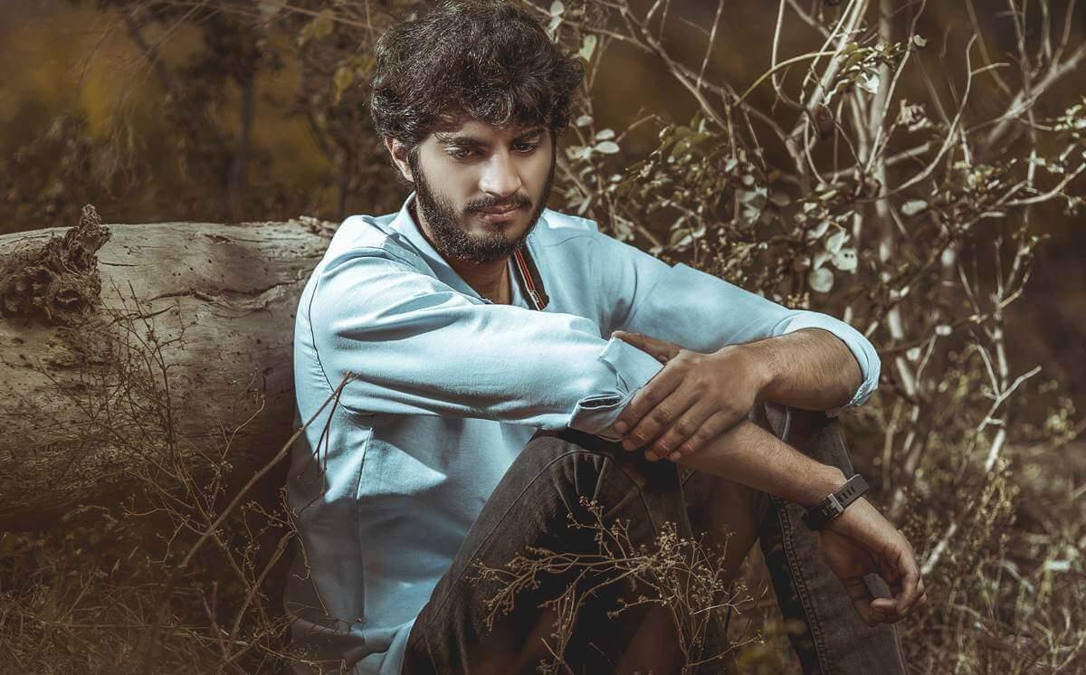 ohne Freunde - Mann sitzt alleine an einem Baumstamm