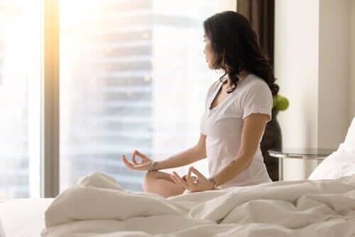 Meditationsübungen - Frau meditiert auf dem Bett