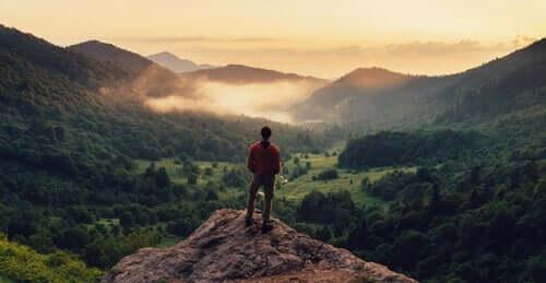 deine Stärken entdecken - Mann an einem Felsvorsprung blickt in die Weite