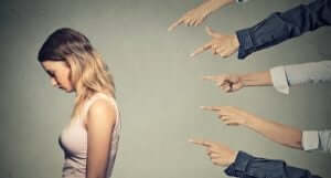 Deviktimisierung - Hände deuten auf eine Frau