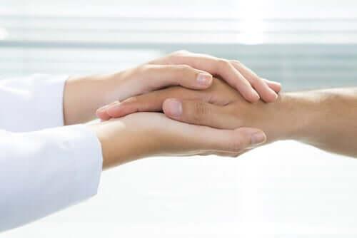 Krankenversicherung - Arzt hält Hand eines Patienten