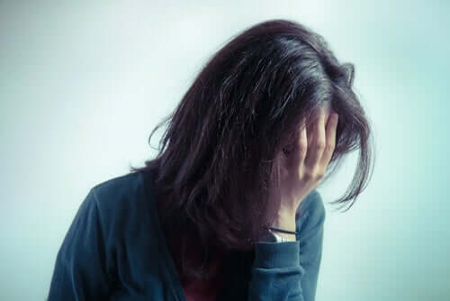 Umweltangst - Frau mit gesenktem Kopf und Hand vor dem Gesicht