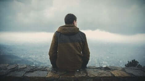 Logotherapie - Mann sitzt auf Berggipfel