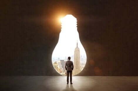 Positives Reframing - Mann betrachtet eine Stadt durch Öffnung in Form einer Glühbirne