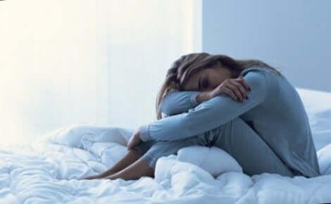 Prämenstruelle dysphorische Störung - Frau sitzt auf einem Bett