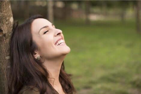 stolz auf dich selbst sein - lächelnde Frau lehnt an einem Baum