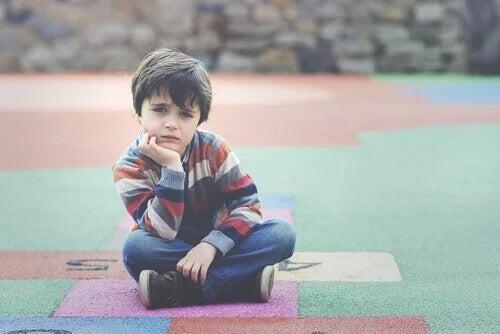 Ein Junge sitzt auf dem Spielplatz und denkt nach.