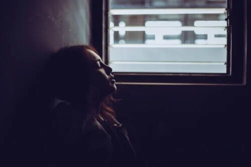 Eine Frau, die Angst hat, sitzt vor einem Fenster.