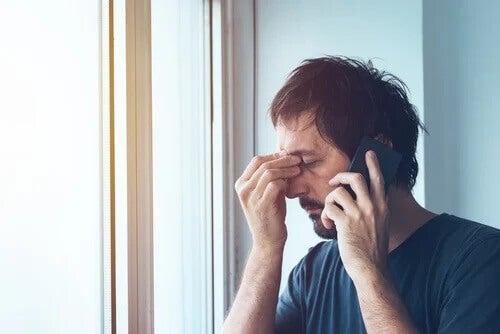 Ein Mann am Handy reibt sich gestresst die Augen.