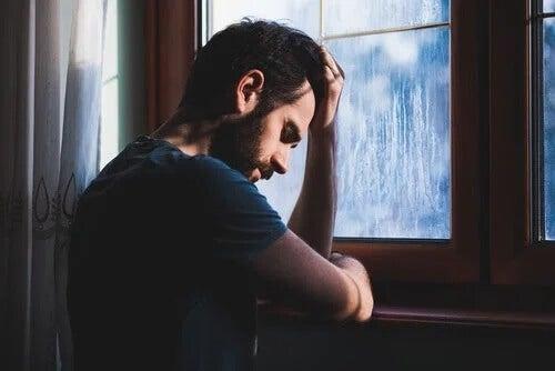 Ein trauriger Mann vor einem Fenster an einem regnerischen Tag.