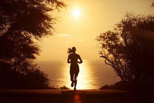 Laufen als Form der Meditation: Eine Frau läuft in den Sonnenuntergang.