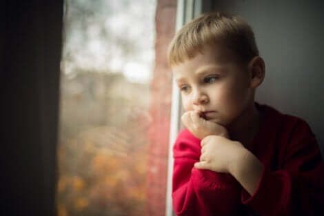-Mit einem Kind über den Tod sprechen - trauriger Junge am Fenster