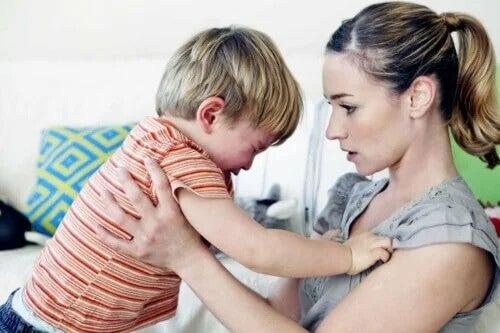 Mutter hält ihr wütendes Kind, bis es sich beruhigt. Wutanfälle sind in der Kindheit häufig.