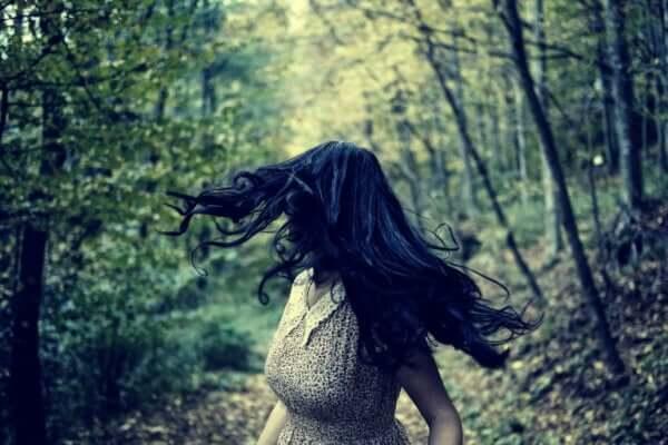 Atavistische Ängste - Frau rennt im Wald und blickt hinter sich