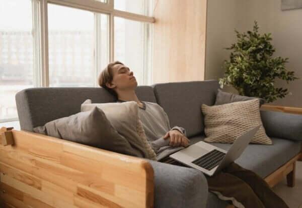 Extreme Müdigkeit - Mann schläft auf Sofa mit Laptop auf den Beinen