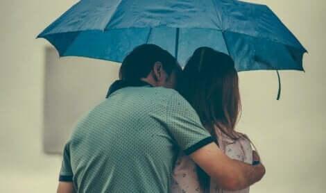 Unreife und reife Liebe - Paar unter einem Regenschirm