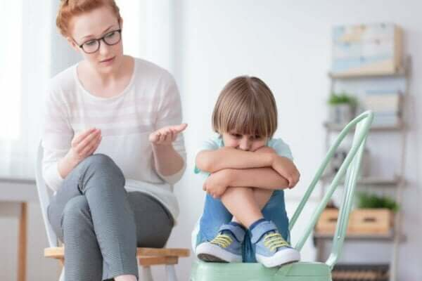 Desintegrative Störung - zusammengekauertes Kind auf einem Stuhl, zu dem eine Frau spricht