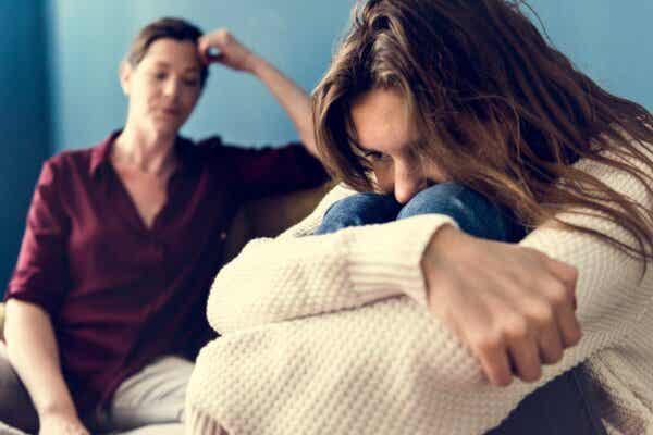 Rebellische Teenager - Mutter mit zusammengekauerter Tochter