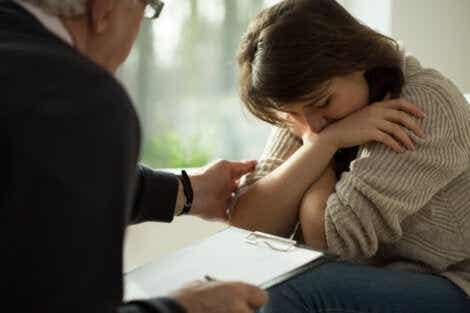 Einen Psychologen aufsuchen - traurige Frau wird getröstet