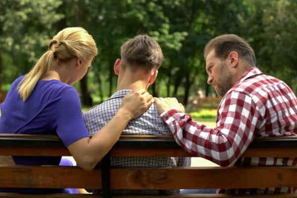 Rebellische Teenager - Eltern mit Sohn auf einer Bank