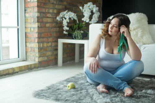 Die Verhaltensaktivierung beim Abnehmen - Frau sitzt auf dem Boden, neben sich einen Apfel